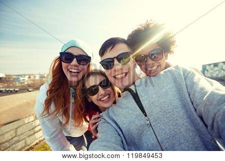 tourism, travel, people, leisure and technology concept - group of smiling teenage friends taking selfie on city street