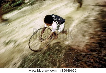 Boy In School Uniform Runs Back Home Playing With A Wheel Of A Bicycle