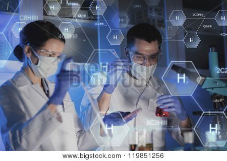 science, chemistry, biology, medicine and people concept - close up of young scientists with pipette and flasks making test or research in clinical laboratory over hydrogen chemical formula