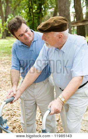 Adult son caring for his aging father who is confined to a walker.