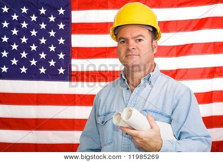 Construction worker with blueprints in front of an American flag.  Photographed in front of the flag, not a composite image.