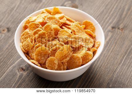 Cornflakes In White Bowl On Gray Wooden Table