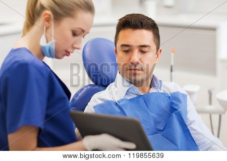 people, medicine, stomatology and health care concept - female dentist showing tablet pc computer to male patient at dental clinic office