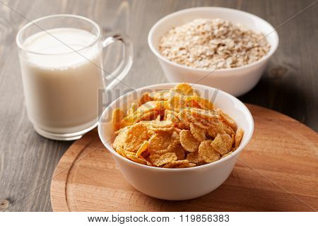 Oatmeal, Cornflakes And Glass Of Milk On Wooden Table