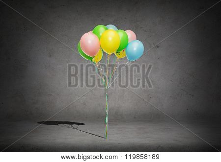 holidays, birthday and party concept - bunch of colorful helium balloons on strand over concrete room background