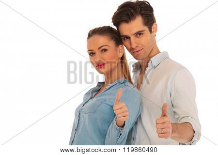 close portrait of man behind woman showing both the thumbs up sign in isolated studio background and looking at the camera