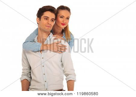 girlfriend holding man from behind while both look away from the camera in isolated studio background