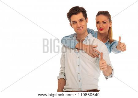 woman holding man from behind while both show thumbs up sign looking at the camera in isolated studio background