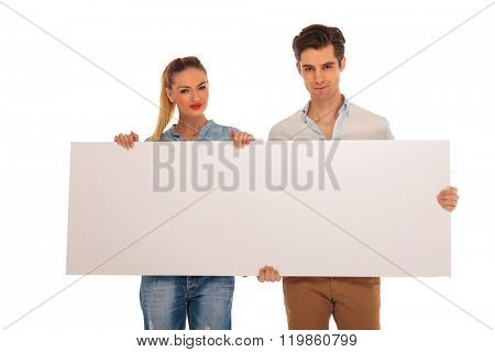 close portrait of cute couple holding a white blank billboard in isolated studio background while looking at the camera