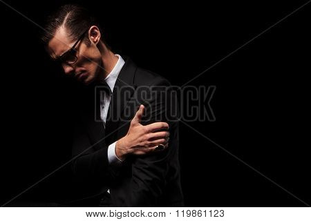 side view of classy smart man in black suit posing looking down while touching his arm in dark studio background
