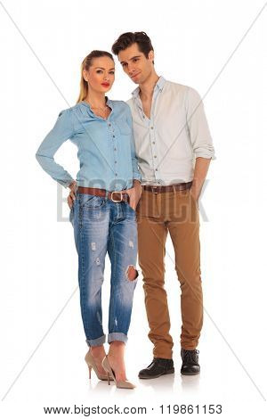 casual cute couple posing in white isolated studio background. woman with hand in pocket looking at the camera while man with hand in pocket is looking away