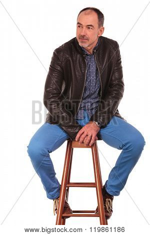 mature man in leather jacket posing seated on chair with legs open while looking away from the camera in isolated studio background