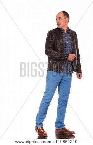 mature elegant man in leather jacket walking and turning in isolated studio background while looking away from the camera