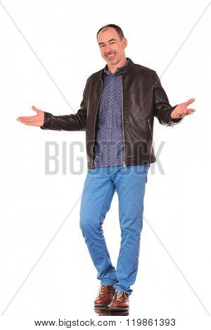 mature casual senior in leather jacket walking and welcoming with both hands while smiling at the camera in isolated studio background