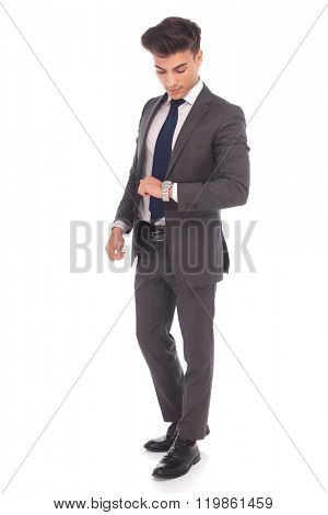 full body picture of a young business man checking time on his watch on white studio background