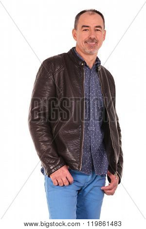 side portrait of caucasian mature man posing with both hands in pockets while smiling at the camera in isolated studio background