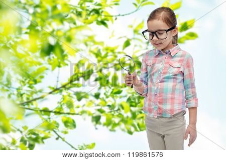 childhood, environment, ecology, discovery and people concept - happy little girl in eyeglasses with magnifying glass over green natural background