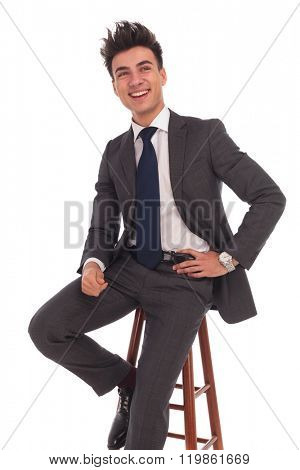 laughing young business man sitting on a chair and looks to side on white background