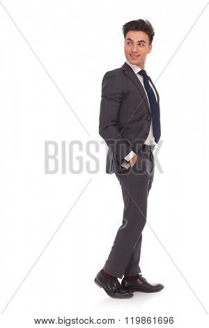 smiling young business man standing with hands in his pockets and he looks back over his shoulder , isolated on white background