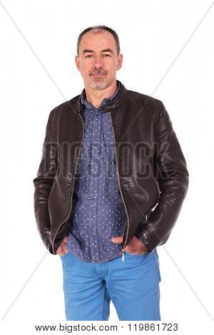 side portrait of confident man in leather jacket posing with both hands in pockets while looking at the camera in isolated studio background