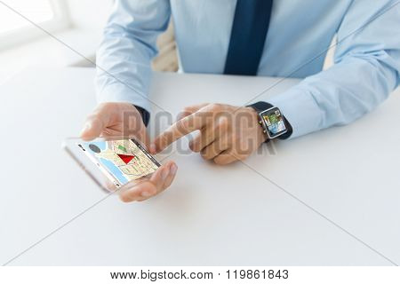 business, technology, navigation and people concept - close up of male hand holding and showing transparent smart phone and watch at office with gps navigator map on screen