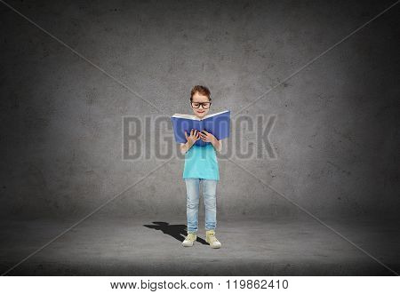 childhood, school, education, vision and people concept - happy little girl in eyeglasses reading book over concrete room background