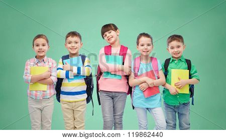 childhood, preschool education, learning and people concept - group of happy smiling little children with school bags and notebooks over green chalk board background