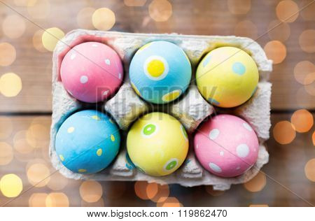 easter, holidays, tradition and object concept - close up of colored easter eggs in egg box or carton wooden surface