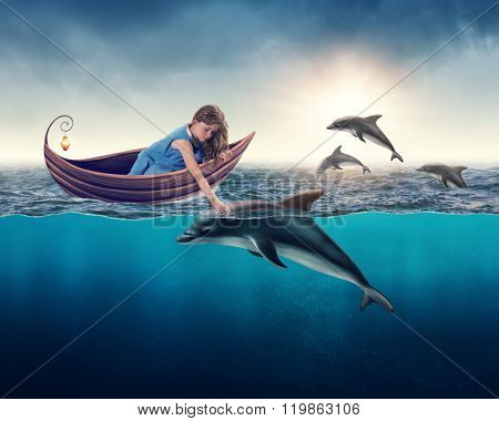 Little girl playing with dolphin