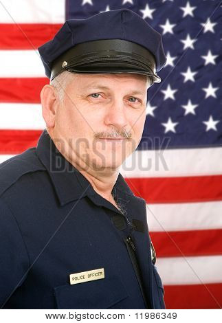 Handsome mature policeman in uniform, against an American Flag.