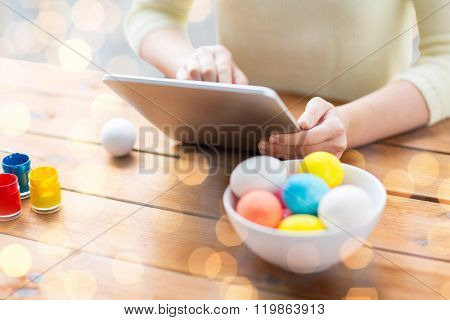 easter, holidays, technology and people concept - close up of woman hands with tablet pc computer, easter eggs and colors