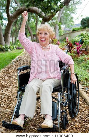 Disabled senior lady in pink, excited about achieving her health goals.