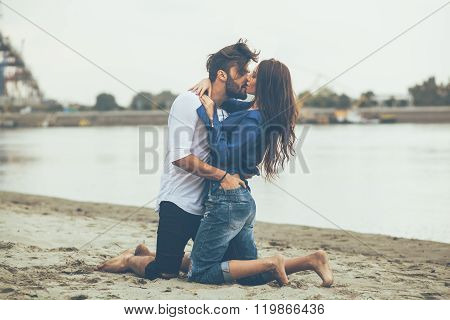 Young Couple Kissing On The Sand By The River