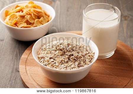 Oatmeal, Cornflakes And Glass Of Milk On Wooden Board