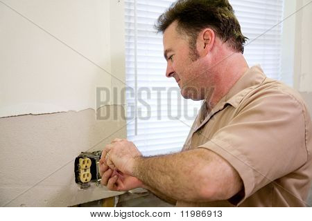 Electrician repairing an electrical outlet.  Horizontal with room for text.  Model is a licensed Master Electrician and all work is being performed according to industry code and safety standards.
