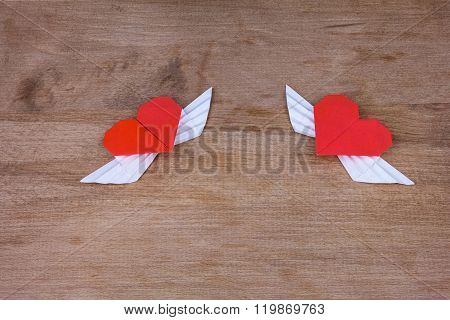 Origami hearts with wings on a wooden background. Two hearts.