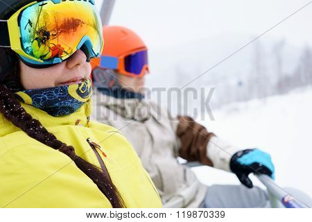 Couple sitting on chairlift in mountain resorts.