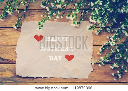 Happy Mothers Day On Brown Paper With White Flower On Wooden Board