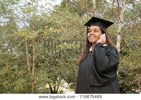 Female graduate using a cellular phone
