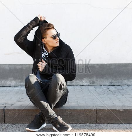 Young Stylish Guy In Sunglasses Sitting On The Curb On The Background Of A White Wall.