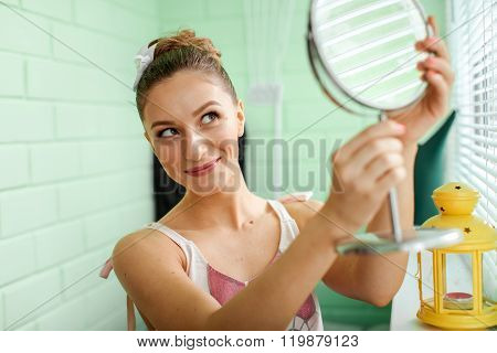 Girl preens in front of mirror