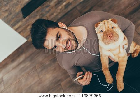 Man Holding Shar Pei Puppy And Listening To Music