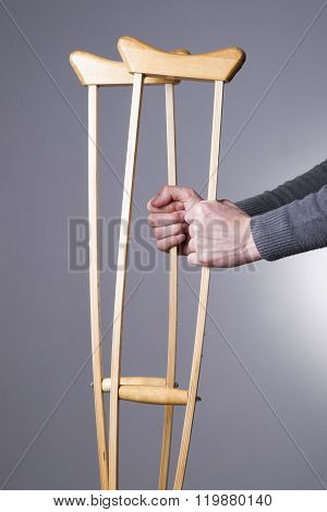 Man With Crutches On A Gray Background