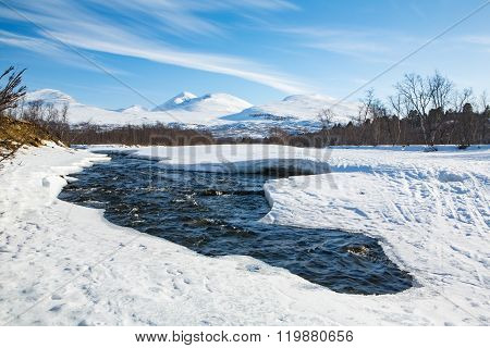 Winter River In The North Of Sweden With Mountains In Background
