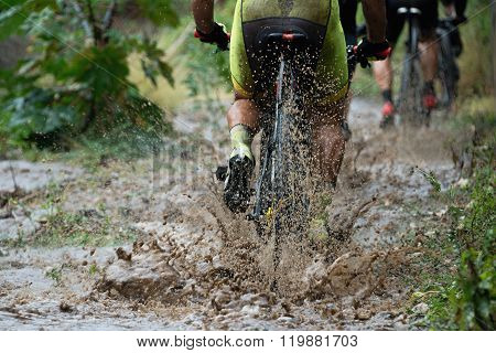 Mountain bikers driving in rain upstream creek