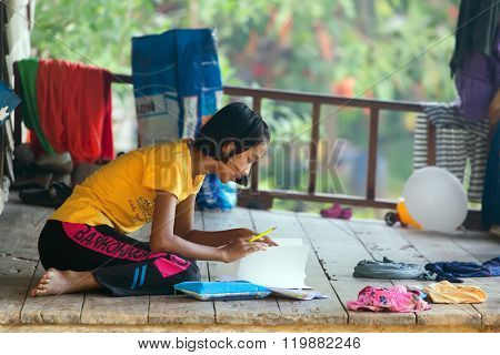 KO MOOK ISLAND, THAILAND, JANUARY 06, 2016 : A young girl is doing her homework, sitting outside on the home wooden terrace in Ko Mook island, Thailand