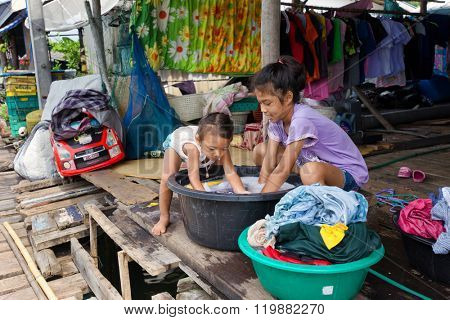 AO SALAT, THAILAND, JANUARY 31, 2016 : Two sisters are hand washing the family laundry in front of the home in Ao Salat fishing village, Ko Kood island, Thailand