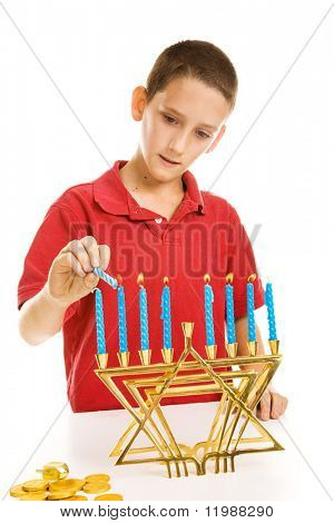 Young boy lighting the menorah for Hanukkah.  Isolated on white.