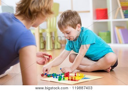 Mother and her son playing in board game