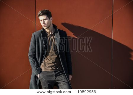 Young Man in a Winter Outfit Leaning on Red Wall